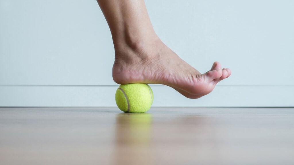 Faszientraining bei Plantarfasziitis - Ausrollen der Fußsohle mit Ball